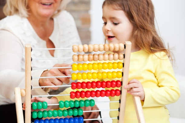 A lady and young girl using a wooden abacus